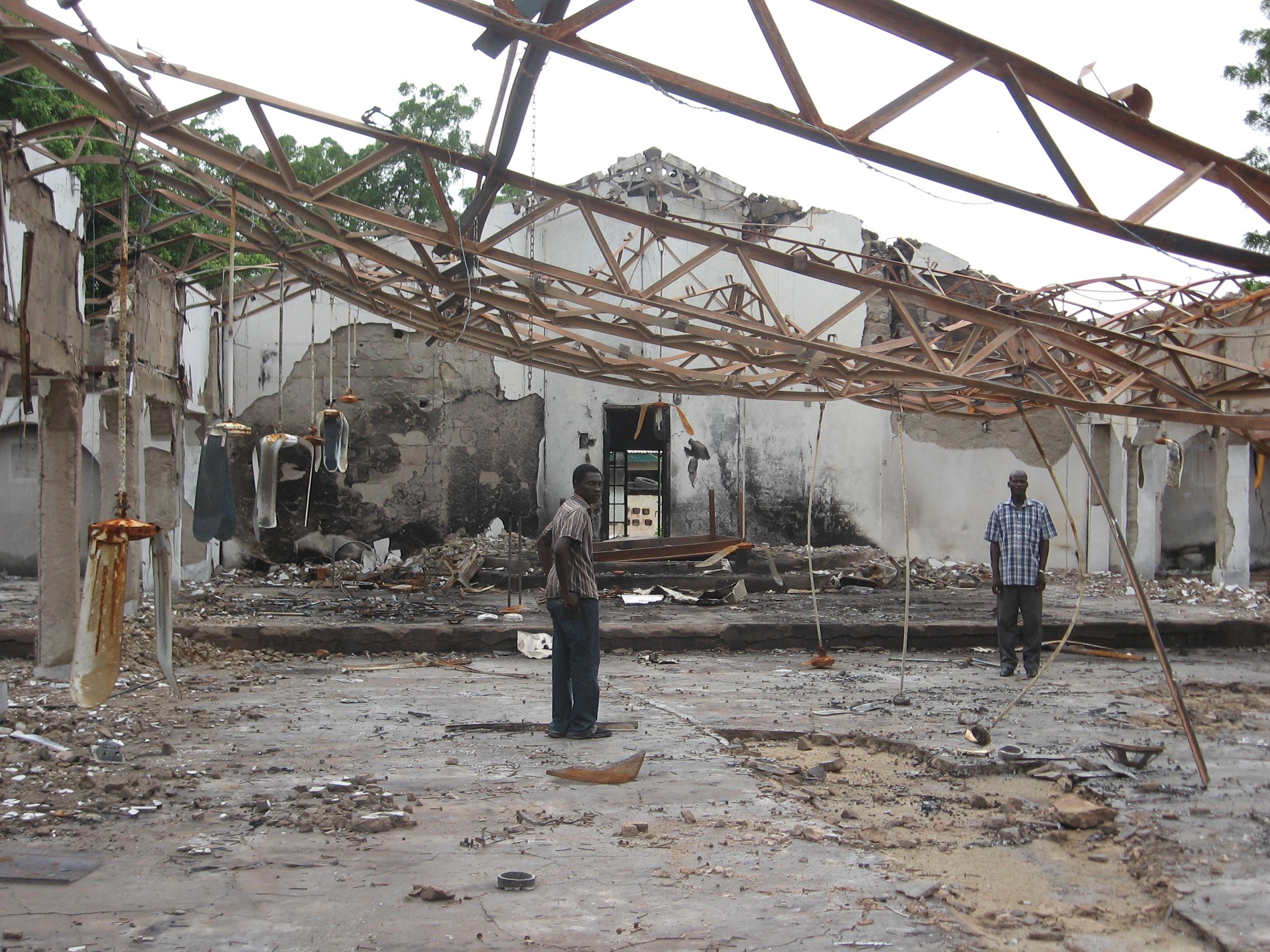 Die Überreste der von Boko Haram ausgebrannten EYN-Kirche in Maiduguri/Wulari; Gemeindemitglied (links) und Gemeindepfarrer Yuguda Z. Mdurvwa. Foto: Mission 21/Jochen Kirsch, Meehyun Chung.